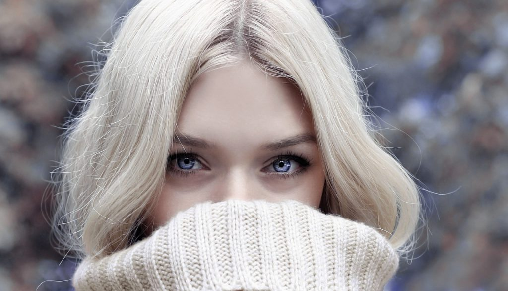 A pretty blonde girl covering her face.